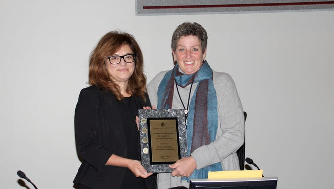 Finance director Marina Neumaier and treasurer Marjorie Banner with the certificate for excellence in financial reporting.