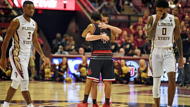 Louisville Cardinals guard Quentin Snider (4) embraces guard Ryan McMahon (30) after winning the game against the Florida State Seminoles at the Donald L. Tucker Civic Center.