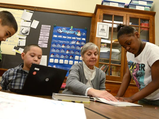 Nicolet Elementary School principal Becky Swanson works with students, from left, Juan Madrigal, Antwan Hollis, and Rahuina Smith, during a reading assignment Thursday in Cassandra Butry's second grade classroom at Nicolet Elementary School.