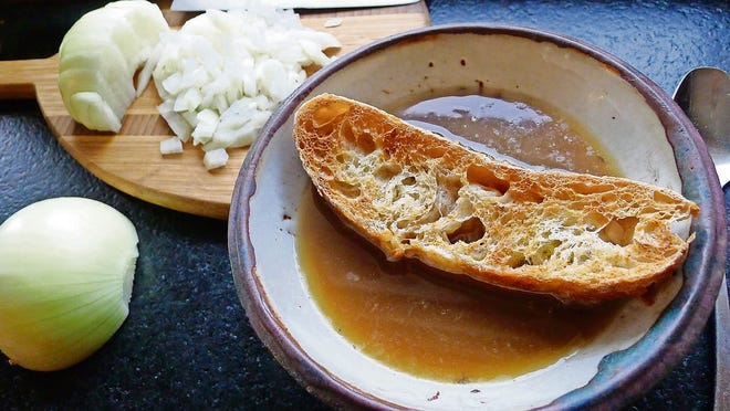 A crusted bowl of French onion soup, with minced onions in the background.