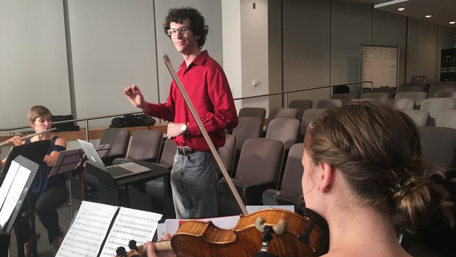 "Graduate-student composer Zachary Bush conducts a rehearsal for a new piece inspired by research into Alzheimer's disease as part of an Arizona State University Biodesign Institute project dubbed ""Science Exposed."""