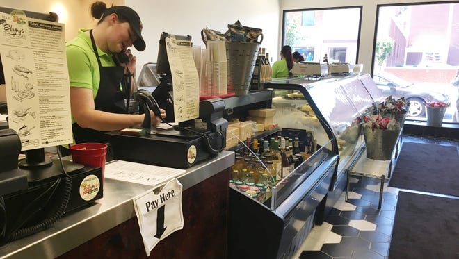 Employee Sophie Militello of Fremont takes an order over the phone at Elroy's Deli Market in downtown Fremont.