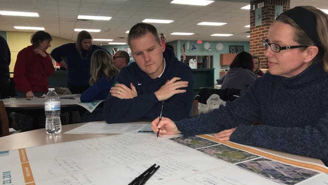 Kevin May and Jen Krohn, both of Waukesha, add questions and comments to a feedback sheet Tuesday, Jan. 23, at Les Paul Middle School in Waukesha. The two were among about 50 people who took part in a focus group to provide feedback to the district on its long-range facilities plan.