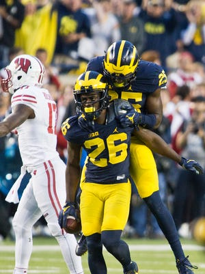 Michigan cornerback Jourdan Lewis (26) celebrates his interception of a pass intended for Wisconsin receiver George Rushing with teammate safety Dymonte Thomas (25) in the fourth quarter at Michigan Stadium on Saturday.