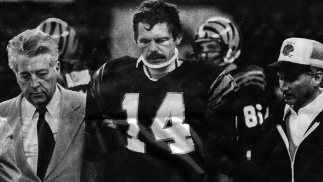 "October 11, 1983: Bengals quarterback Ken Anderson leaves the field at Riverfront Stadium wearing a neck brace after he was tackled by the face mask during their ""Monday Night Football"" game with the Steelers."