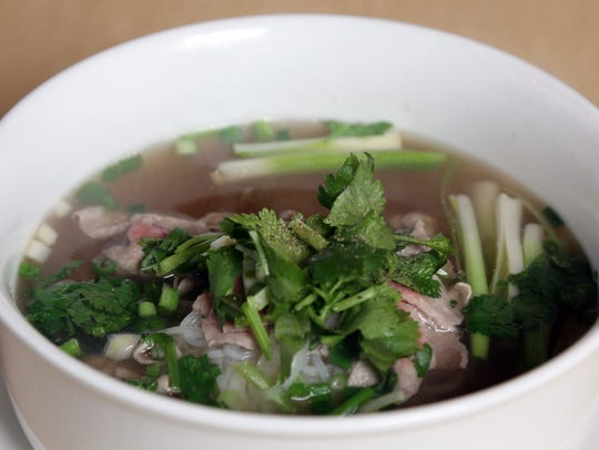 Rare beef pho topped with zestly herbs at Love, Peace