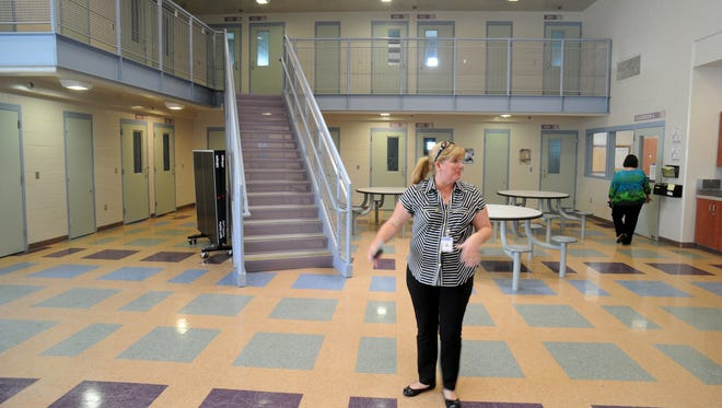 Division manager Michelle Steinberger looks around the day room and sleeping room in one section of the juvenile justice complex in El Rio.