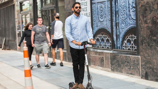 Sunny Patel, 21, of Troy takes a Bird scooter for a spin in downtown Detroit Friday. The new rentable Bird scooters are now available via smart phone app in Detroit on Friday, July 27, 2018. Bird is a dockless scooter-sharing company based in Santa Monica, California.