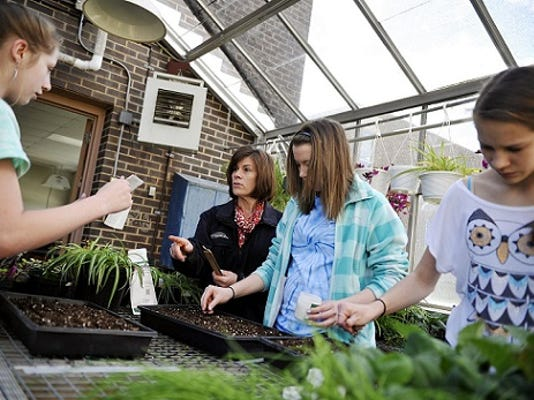 York Daily Record; Northern Middle School agriculture education teacher Carol Richwine, second from left, directs Future Farmers of America club members and eighth-grade students, from left, Lindsay Stefanon, Abby McAleer and Kiersten Staley as they plant carrot seeds in a greenhouse connected to the school.
