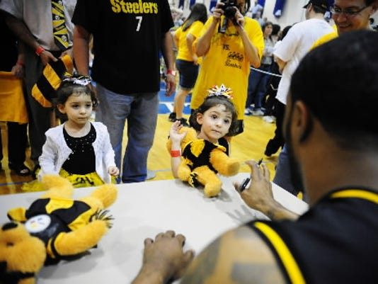 Twins Carrington and Zoey Henry of West Manchester Township, received autographs from Pittsburgh Steelers' Ryan Mundy during halftime at a fundraising basketball game at West York Area High School in March 2012.
