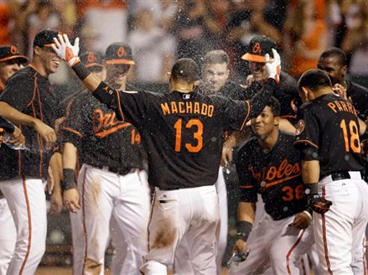 Baltimore's' Manny Machado is sprayed with water by teammates as he approaches home plate after hitting a two-run home run during the 13th inning of a game against the Oakland Athletics on Friday in Baltimore. Baltimore won 8-6.
