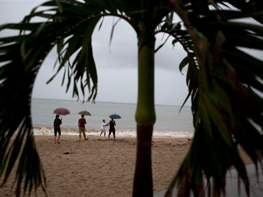 People walk along the beach under a steady rain as they await the arrival of Hurricane Patricia in Puerto Vallarta, Mexico, Friday, Oct. 23, 2015. The storm was homing in on a Pacific coastline dotted with sleepy fishing villages and gleaming resorts, including the popular beach city of Puerto Vallarta and the port of Manzanillo.  (AP Photo/Rebecca Blackwell)