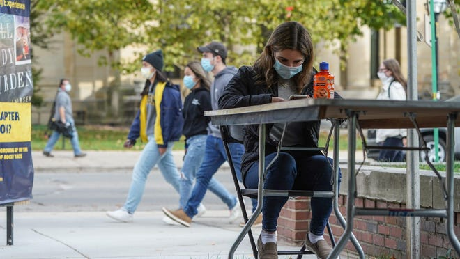 University of Michigan junior Rachel Ellis of San Diego waits for a friend in a study tent outside of the Michigan Union building on campus in Ann Arbor on Tuesday, October 20, 2020. Total enrollment in the state's higher education system fell by 3%, a survey of schools by the Detroit Free Press shows.