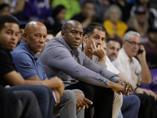 FILE - In this Oct. 4, 2017 file photo Los Angeles Lakers general manager Rob Pelinka, center right, and Magic Johnson watch the team's NBA preseason basketball game against the Denver Nuggets in Ontario, Calif. The Lakers have been fined $50,000 for violating the NBA's tampering rule again. League officials made the announcement Tuesday, Feb. 6, 2018 in response to an interview Johnson did with ESPN. (AP Photo/Jae C. Hong)