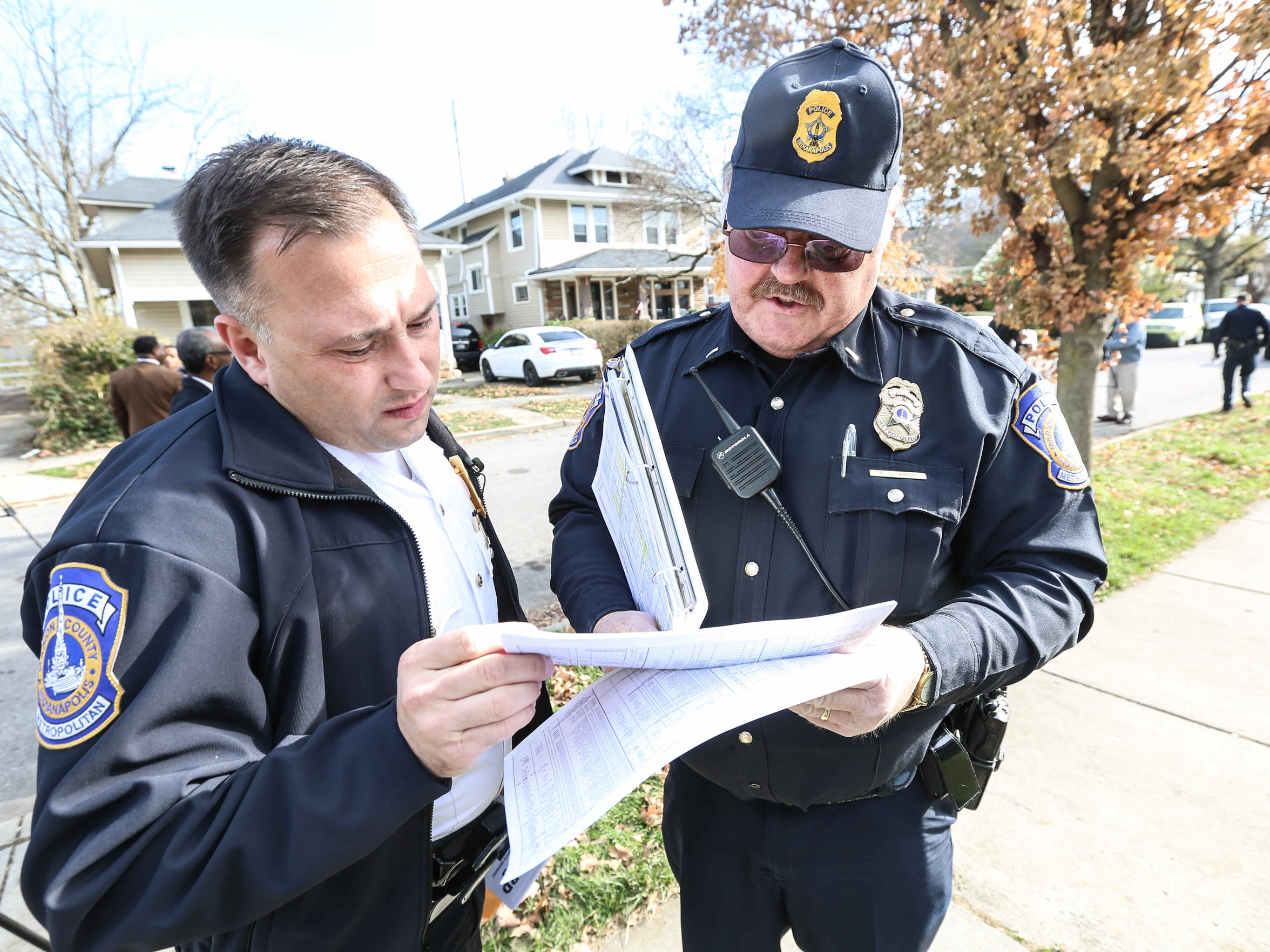 North District Commander Chris Bailey (left) and Lt. Terry Eden met after passing out fliers seeking the public's help in solving the slaying of Deshaun Swanson. IMPD officers met for roll call Nov. 25, 2015, outside the house in the 3900 block of Graceland Avenue where Deshawn, 10, was gunned down while attending a memorial service Sept. 19.