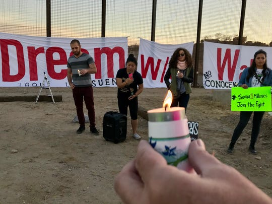 "About 25 people hold a candlelight vigil as they urge solidarity to resist militarization along the U.S.-Mexico border and demand that Congress move on a clean Dream Act without provisions for a border wall. The immigrant rights movement Movimiento Cosecha Texas, area artists and groups from El Paso, Canutillo, Juárez and Las Cruces took part in the protest at 1720 W. Paisano Drive. The group sang and lit candles and hung a banner saying, ""Dream w/o walls"" on the border barrier."