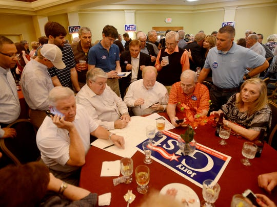Supporters of Jerry Gist gather around a table to listen to and tally results from the Madison County Election Commission during Gist's election watch party on Tuesday.