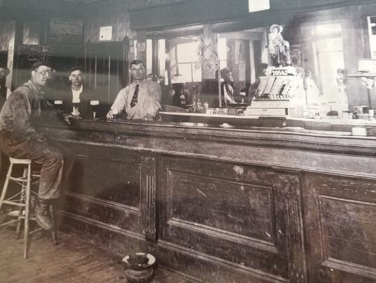A historic picture of a former bar with patrons at