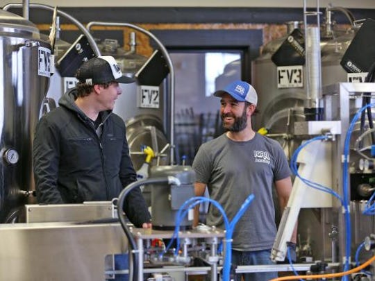 Indiana City Brewing Co. founder Ray Kamstra left) talks with iCan Solutions' founder Luke Brown, before canning begins at the Indianapolis brewery  on Jan. 26, 2016.