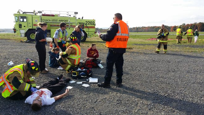 Emergency response workers tend to victims during an aviation disaster drill Saturday morning at the Ithaca-Tompkins Regional Airport.