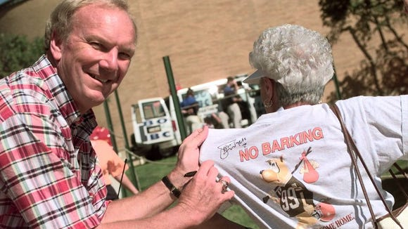 """Sam Wyche signs a """"No Barking"""" t-shirt in 1998."""
