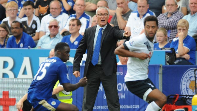 Leicester manager Claudio Ranieri, center, gives instructions to his players from the sidelines during the English Premier League soccer match between Leicester City and Tottenham Hotspur at the King Power Stadium, Leicester, England.
