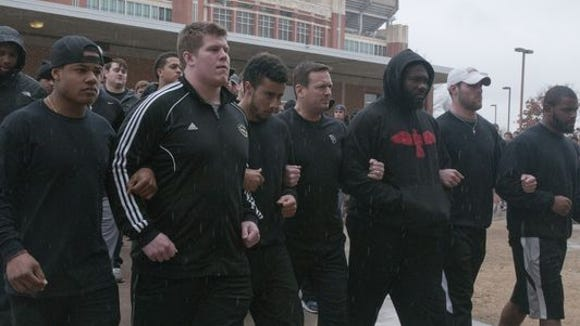 The University of Oklahoma football team (with head coach Bob Stoops in the middle) locked arm and arm in protesting a fraternity using racial slurs that surfaced in a video Sunday.