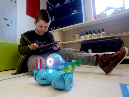 First-grader Owen Traynor programs a toy robot at the