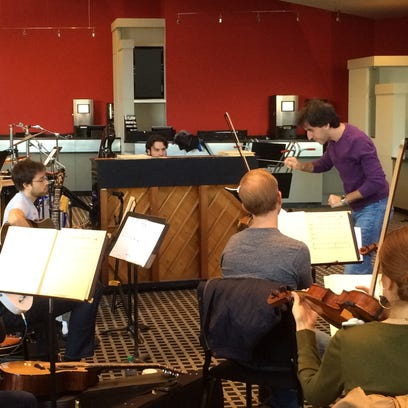 Composer Jason Robert Brown conducts an orchestra rehearsal
