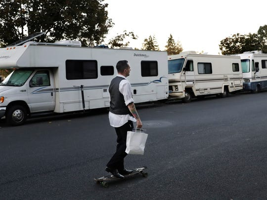 In this photo taken Oct. 5, 2017, a man skates past a row of RVs where people live and sleep in the heart of silicon valley in Mountain View, Calif.