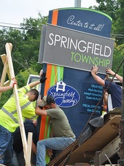 Workers install new gateway sign in Springfield Township.