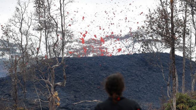 Abe Pedro watches lava shoot out of a fissure on Pohoiki Rd, Friday, May 18, 2018, near Pahoa, Hawii. )