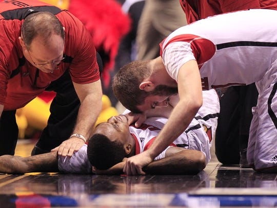 Louisville player Luke Hancock, right, tries to comfort
