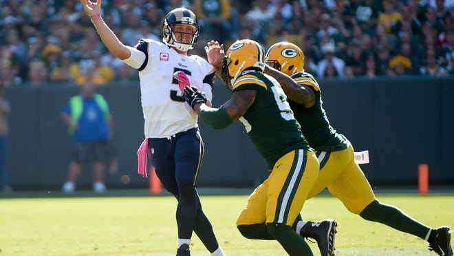 Rams quarterback Nick Foles is harassed by the Packers' Julius Peppers in the third quarter at Lambeau Field Sunday. The Rams lost 24-10 to drop to 2-3.
