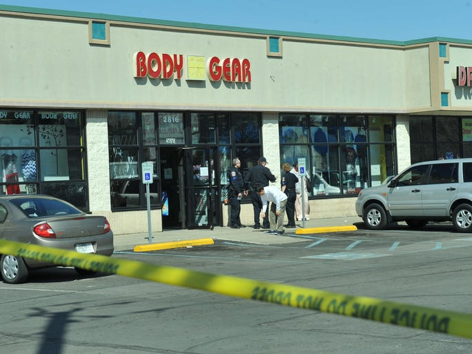 Indianapolis Metropolitan police detectives and officers gather outside Body Gear, 2816 E. 38th St., on March 30, 2014, after two workers at the clothing store were shot during a shoplifting incident. The shooting killed Ho Lee, 36, Noblesville.