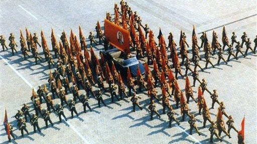 In this April 25, 1997 photo from North Korea's official Korean Central News Agency, distributed by Korea News Service, military parade forms the shape of a star to celebrate the 85th anniversary of leader Kim Il Sung and the 65th anniversary of (North) Korean People's Army in Pyongyang Square, North Korea. The (North) Korean Workers' Party flag, Republic flag and the military flag and the portrait flag of leader Kim Il Sung at the center.