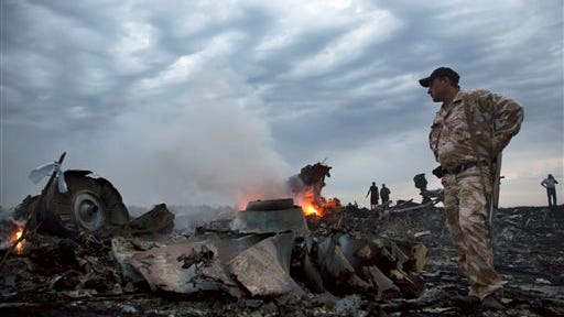 In this July 17, 2014, file photo, people walk amongst the debris, at the crash site of a passenger plane near the village of Hrabove, Ukraine. More travelers are flying than ever before, creating a daunting challenge for airlines: continue to keep passengers safe in an ever more crowded airspace.