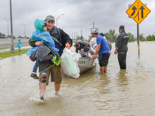 Volunteers and first responders work together to rescue residents from rising flood waters in Houston, Tuesday, Aug. 29, 2017. (Scott Clause/The Daily Advertiser via AP)