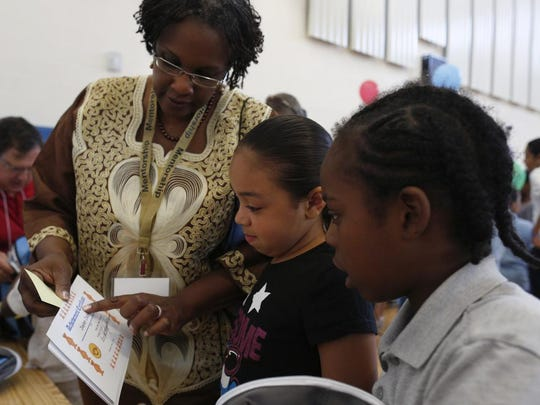 Sandra Fink, left, a retired Rochester School District science teacher, helps Jaelyn Jackson, 8, center, and Lamar Scott, 8, read their certificates of completion at a celebration of the Help Me Read program at School 17.