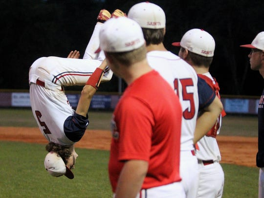 Wakulla Christian's Destin Todd does a back flip in celebration of the Saints' first playoff win in school history.