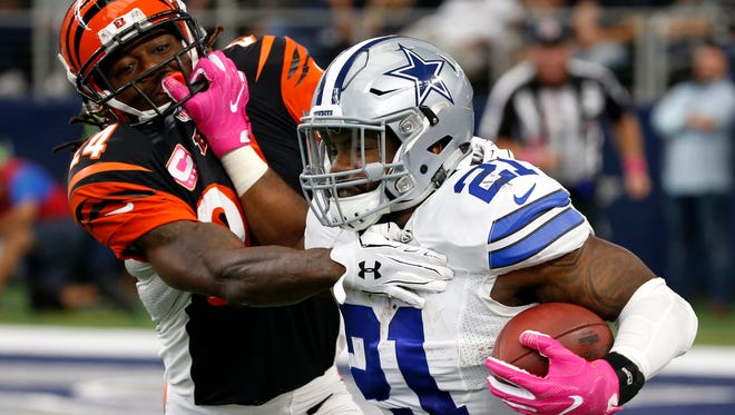 Dallas Cowboys running back Ezekiel Elliott (21) fights off a tackle attempt by Cincinnati Bengals cornerback Adam Jones (24) in the first half of an NFL football game, Sunday, Oct. 9, 2016, in Arlington, Texas.