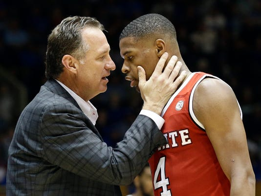 """FILE - In this Jan. 23, 2017, file photo, N.C. State's head coach Mark Gottfried speaks with Dennis Smith Jr. during the second half of an NCAA college basketball game in Durham, N.C. Bank records and other expense reports that are part of a federal probe into college basketball list a wide range of impermissible payments from agents to at least two dozen players or their relatives, according to documents obtained by Yahoo Sports. A balance sheet from December 2015 lists several payments under """"Loan to Players,"""" including $43,500 to Dallas Mavericks guard Dennis Smith, who played one season at North Carolina State in 2016-17. Another document says Smith received a total of $73,500 in loans, and indicated options to recoup the money after Smith didn't sign with ASM. (AP Photo/Gerry Broome, File)"""