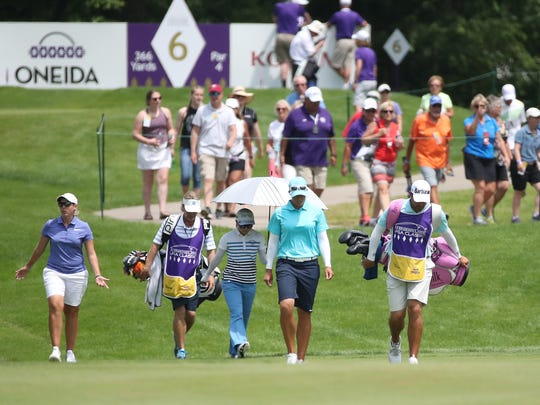 Spectators follow final group players Ashleigh Buhai, left, Ayako Uehara and Katherine Kirk during Sunday's final round of the Thornberry Creek LPGA Classic in Hobart.