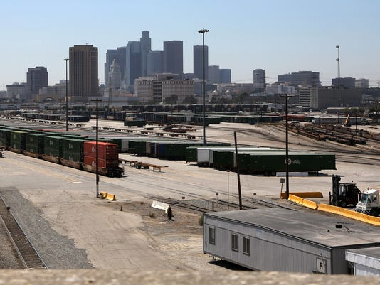 The Union Pacific Intermodal rail yard is viewed with the Los Angeles skyline on Friday, Aug. 28, 2015. The vast extension of land could be repurposed as the centerpiece of the proposed $1 billion residential village for the 2024 Olympic Games bid. But with a deadline to submit a U.S. candidate for the 2024 Games just 18 days away, the plan remains a mystery in many ways. The sprawling Olympic Village, to be built with mostly private funds, is tethered to a series of financial assumptions and question marks. (AP Photo/Richard Vogel)