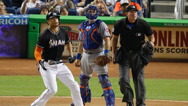 Miami Marlins' Giancarlo Stanton, left, watches his two-run home run in the third inning in front of New York Mets catcher Travis d'Arnaud during a baseball game in Miami, Saturday, July 23, 2016.
