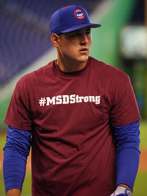 Cubs first baseman Anthony Rizzo and teammates wear shirts to honor the school shooting victims of the Marjory Stoneman Douglas High School in Parkland, Fla. before their season opener in Miami.