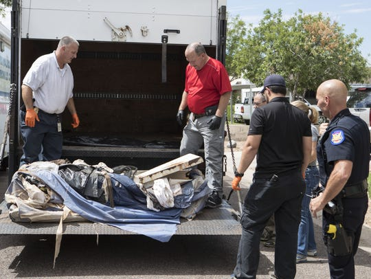 Officers carry objects out of a Phoenix house where