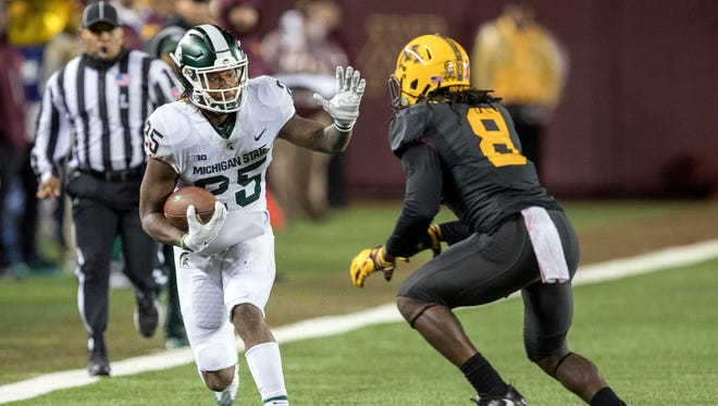 Michigan State Spartans wide receiver Darrell Stewart Jr. (25) rushes with the ball after making a catch and attempts to get around Minnesota Golden Gophers defensive back Duke McGhee (8) in the second half at TCF Bank Stadium.