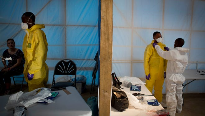 Prospective health care workers in the Kerry Town Ebola Treatment Center in Sierra Leone being tested on their personal protection equipment.