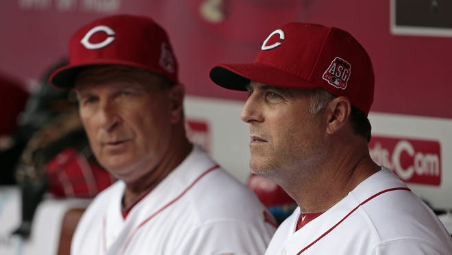 Third base coach Jim Riggleman, left, and Cincinnati Reds manager Bryan Price (38) talk in the dugout prior to the first inning.